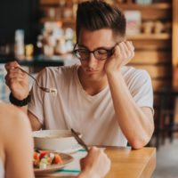 Unhappy man with eating problem staring at food in cafe