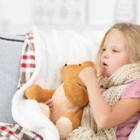 Little girl coughing holding her teddy bear